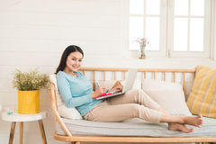 Happy young asian entrepreneur working with a laptop at home. Royalty Free Stock Photos