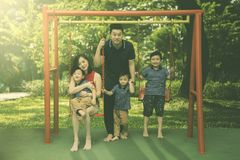 Happy young Asian family of four having a quality time at playground`s swing Stock Photography