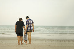 Happy Young Asian Family Having Fun Walking on tropical beach va. Happy Young Asian Family Walking on beach vacation outdoors, vintage tone, Shallow DOF, Concept Royalty Free Stock Photo