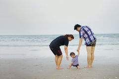 Happy Young Asian Family Having Fun Walking on at tropical beach Stock Photography