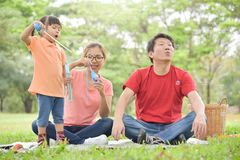 Asian family are blowing soap bubbles together. Happy young Asian family and their daughter are blowing soap bubbles together in nature at park outdoor. Family stock photo