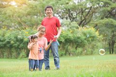 Asian family are blowing soap bubbles together. Happy young Asian family and their daughter are blowing soap bubbles together in nature at park outdoor. Family royalty free stock photography