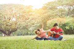 Happy Asian family having fun. Happy young Asian family with their daughter having fun in nature at park outdoor stock image