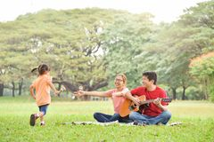 Happy Asian family having fun. Happy young Asian family with their daughter having fun in nature at park outdoor stock photos