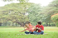 Happy Asian family having fun. Happy young Asian family with their daughter having fun in nature at park outdoor royalty free stock image