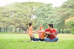 Happy Asian family having fun. Happy young Asian family with their daughter having fun in nature at park outdoor stock photo