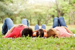 Happy Asian family having fun. Happy young Asian family with their daughter are lying on green grass in nature at park outdoor. Holiday and Having fun stock images