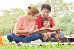 Happy Asian family having fun. Happy young Asian family with their daughter Reading a book. People having fun in nature at park outdoor stock photography