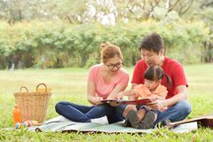 Happy Asian family having fun. Happy young Asian family with their daughter Reading a book. People having fun in nature at park outdoor stock photos