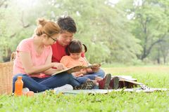 Happy Asian family having fun. Happy young Asian family with their daughter Reading a book. People having fun in nature at park outdoor royalty free stock photography