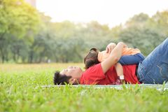 Happy young Asian father and his daughter are hugging together a. Nd sleeping on the grass in nature at park outdoor. Family stock image