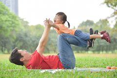 Asian father and his daughter playing together. Happy young Asian father and his daughter lying on the grass and playing together in nature at park outdoor royalty free stock images