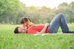 Asian father and his daughter playing together. Happy young Asian father and his daughter lying on the grass together in nature at park outdoor. Family. Love royalty free stock photos