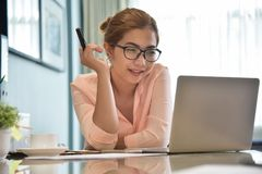 Happy Young Asian Female creative designer working. Happy Young Asian Female creative designer wear glasses working with a laptop computer at her workplace. A stock photos