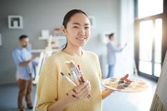 Girl at painting lesson. Happy young Asian female painter with palette and paintbrushes standing by easel in studio of arts stock photo