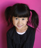Happy young Asian girl. Portrait of happy Asian girl with pigtails, purple studio background Royalty Free Stock Photo