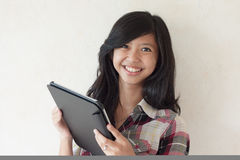 Happy young asian girl holding a tablet pc. Represent both business and educational matter Royalty Free Stock Photos