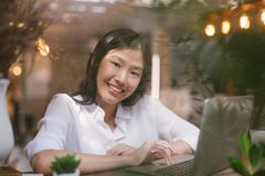 Happy young Asian girl working at a coffee shop with a laptop view through glass. royalty free stock photo
