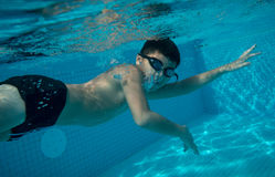 Happy young asian kid with swim goggles underwater. Front crawl in middle of swimming pool, smile relax face swimmer have fun activity Royalty Free Stock Photo