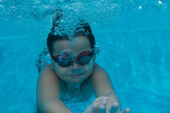 Happy young asian kid with swim goggles underwater. Front crawl in middle of swimming pool, smile relax face swimmer have fun activity Stock Photo