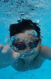 Happy young asian kid with swim goggles underwater. Front crawl in middle of swimming pool, smile relax face swimmer have fun activity Stock Photography