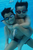 Happy young asian kid with swim goggles underwater Royalty Free Stock Photos