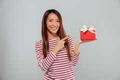 Happy young asian lady standing isolated holding gift and pointing. Royalty Free Stock Photos