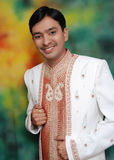 Happy young Asian man. Half body portrait of happy young Asian man in traditional clothes,; colorful background Stock Image