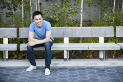 Happy young asian man on bench Royalty Free Stock Photography