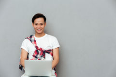 Happy young asian man over grey background using laptop Stock Photos