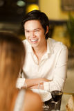 Happy young Asian man in a restaurant. Happy young Asian man smiling and laughing with friends in a restaurant Royalty Free Stock Photo