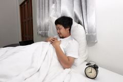 Happy young Asian man sleeping on the white bed with sweet dream.  Stock Photography