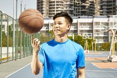 Young asian man playing with basketball. Happy young asian man spinning a basketball on finger Stock Images