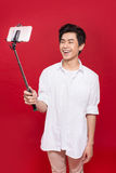 Happy young asian man taking self portrait photography through s. Mart phone over red background Royalty Free Stock Image