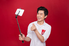 Happy young asian man taking self portrait photography through s Royalty Free Stock Images