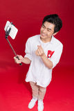Happy young asian man taking self portrait photography through s. Mart phone over red background Royalty Free Stock Images
