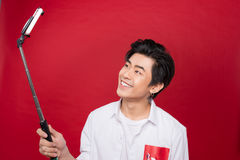 Happy young asian man taking self portrait photography through s. Mart phone over red background Stock Image