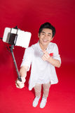 Happy young asian man taking self portrait photography through s. Mart phone over red background Royalty Free Stock Photography