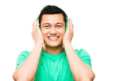 Happy young Asian student with headphones. Listening to music Royalty Free Stock Photography