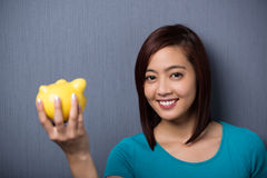 Happy young Asian student holding a piggy bank Royalty Free Stock Images