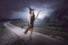 Happy young asian witch with a broom getting ready to fly Stock Photo