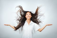 Happy young Asian woman with beautiful flying long hair. Happy young Asian woman with beautiful flying long dark hair. Portrait of carefree joyful girl smiling stock images