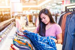 Happy young asian woman checking a price tag on shirt in mall or clothing store royalty free stock image