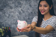 Happy young asian woman doing online shopping. Happy woman saving money in a piggy bank, Saving money concept Royalty Free Stock Photo