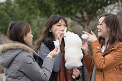 Happy young Asian woman eating cotton candy with her friends Stock Photo