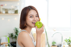 Happy Young Asian Woman Eating Green Apple on Kitchen. Diet. Die Royalty Free Stock Photography