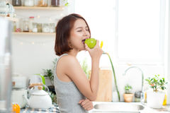 Happy Young Asian Woman Eating Green Apple on Kitchen. Diet. Die Royalty Free Stock Image