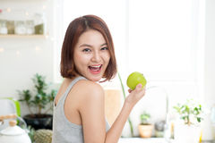 Happy Young Asian Woman Eating Green Apple on Kitchen. Diet. Die Royalty Free Stock Photos