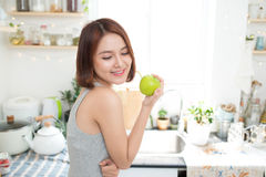 Happy Young Asian Woman Eating Green Apple on Kitchen. Diet. Die Stock Images