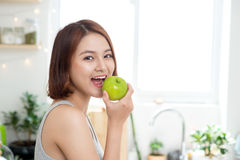 Happy Young Asian Woman Eating Green Apple on Kitchen. Diet. Die Stock Photography